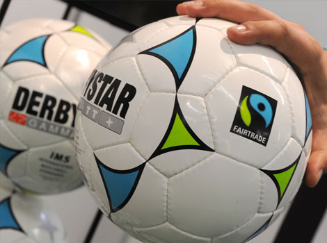 "A man holds a ""Derbystar"" football, manufactured in Pakistan, in Dortmund, western Germany, during the ""Fair 2011"" an exhibition for fair trade."