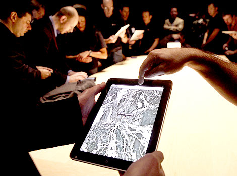 "People look at a view of Google Maps on the new ""iPad"" during the launch of Apple's new tablet computing device in San Francisco, California"