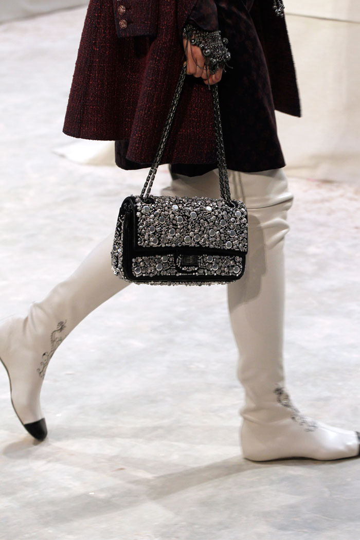 Chanel's trademark knee high boots make a stylish contrast of textures with the sequined bag.