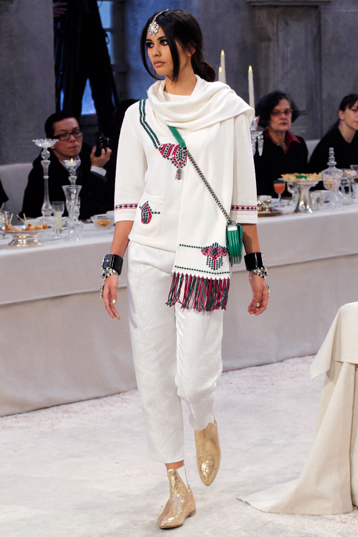 A day look teams simple white pants with a detailed sweater and scarf, finished with sparkling gold boots.