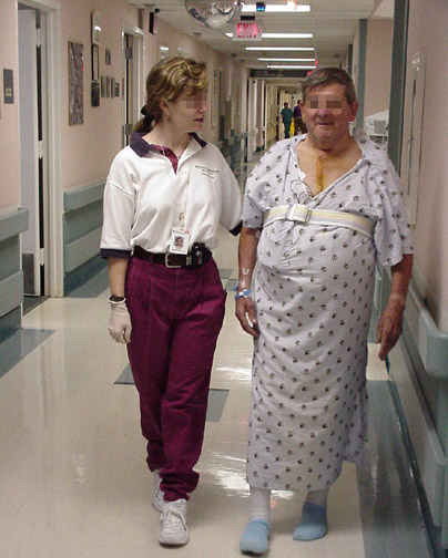 Phase 1: A patient walking in the hallway with a physical therapist following bypass surgery.